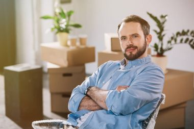 Handsome bearded man sitting with crossed arms and looking at camera while relocating in new office stock vector