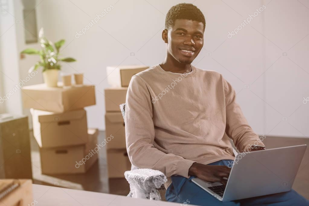 Handsome african american man using laptop and smiling at camera while sitting in new office during relocation