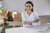 šťastná mladá podnikatelka se usmívá na kameru při sezení na pracovišti v nové kanceláři