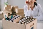Fotografie Detailní pohled box s kancelářské potřeby a podnikatelka sedí za