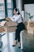 s úsměvem mladá podnikatelka v sluchátka pomocí chytrého při rozbalení krabice v nové kanceláři