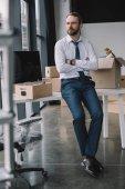 podnikatel s překřížením rukou sedí na stole a koukal v nové kanceláři během přemístění