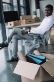 vista ravvicinata della scatola di cartone con forniture per ufficio e uomo daffari afroamericano che si siede dietro nel nuovo ufficio