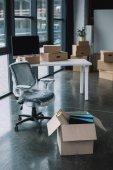 zalomený židle a kartonové krabice v úřadu během přemístění