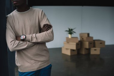 cropped shot of african american man standing with crossed arms and cardboard boxes behind in new office