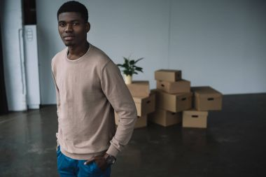 young african american man standing with hands in pockets and looking at camera while moving in new office