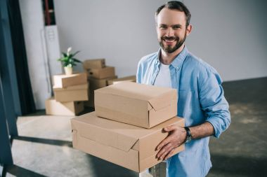 Happy bearded man holding boxes and smiling at camera during relocation stock vector