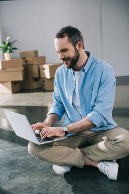 smiling bearded man using laptop while sitting on floor during relocation