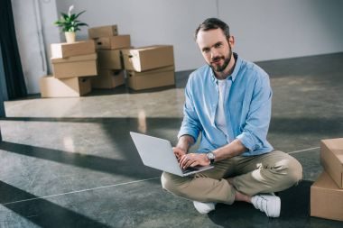 handsome bearded man using laptop and smiling at camera while sitting on floor in new office