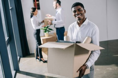 african american businessman holding cardboard box and smiling at camera while colleagues standing behind in new office