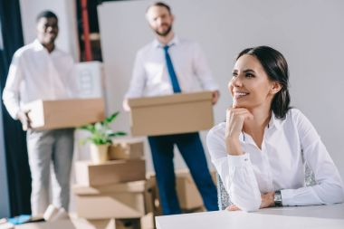 smiling young businesswoman sitting and looking away while male colleagues holding boxes behind in new office