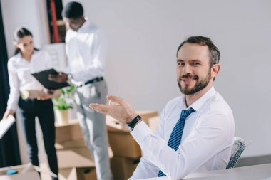 happy businessman smiling at camera while colleagues standing behind in new office