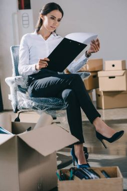 focused young businesswoman holding clipboard while sitting in new office during relocation