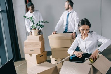young businesswoman unpacking cardboard box and male colleagues standing behind in new office