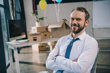 handsome businessman with crossed arms smiling at camera in new office decorated with balloons