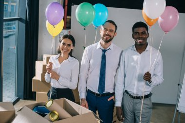 happy multiracial colleagues holding colorful balloons and smiling at camera in new office