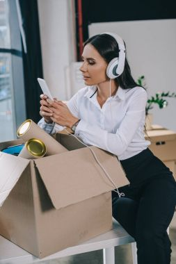 beautiful young businesswoman in headphones using smartphone while unpacking box in new office