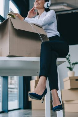 low angle view of smiling young businesswoman in headphones using smartphone while unpacking box in new office