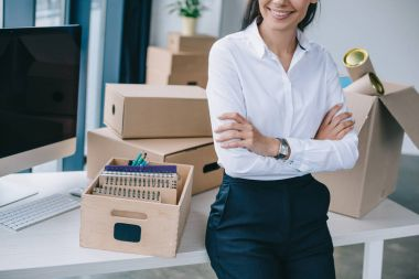 cropped shot of smiling businesswoman with crossed arms sitting on table in new office