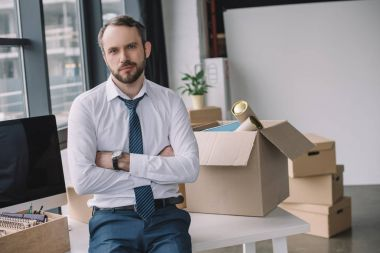businessman with crossed arms looking at camera while sitting on table with boxes in new office