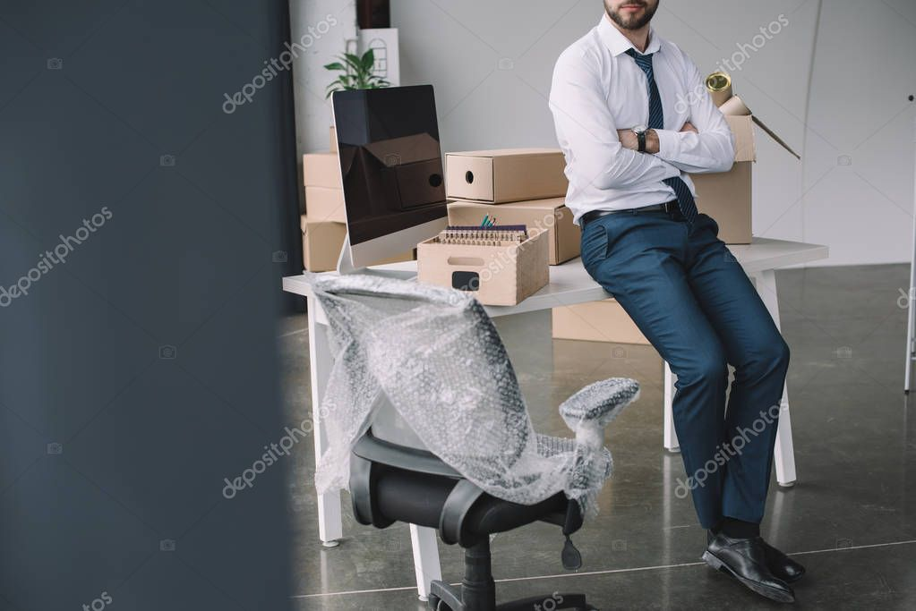 Cropped shot of businessman with crossed arms sitting on table in new office during relocation