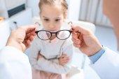 Fotografia immagine potata di oftalmologo proponendo nuovi occhiali per bambino infelice in clinica