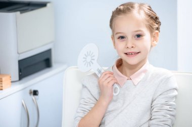 adorable child looking at camera at oculist consulting room