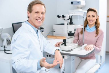 smiling ophthalmologist and patient near slit lamp in clinic