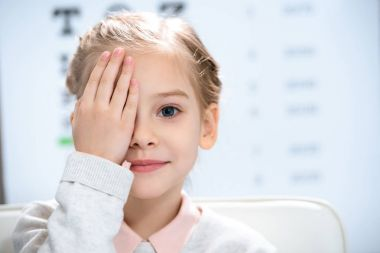 little child closing eye with eye test behind