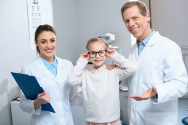 two smiling ophthalmologists and little child in eyeglasses