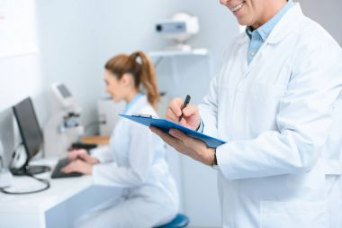 Cropped view of male optometrist writing diagnosis while colleague using with computer in clinic stock vector