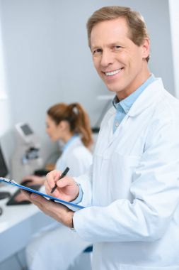 Male optician writing diagnosis while coworker using with computer in clinic stock vector