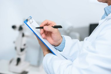 cropped view of optician writing diagnosis in clinic