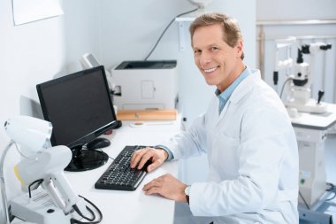 handsome smiling male ophthalmologist working with computer in clinic