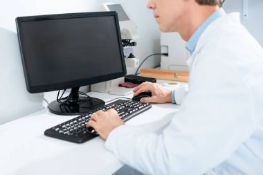 cropped view of male optician working with computer in clinic