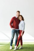 full length view of beautiful redhead couple standing on grass and smiling at camera on grey