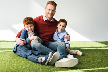 happy redhead father and kids sitting together on grass and smiling at camera on grey