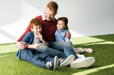 happy father embracing adorable little kids while sitting on grass