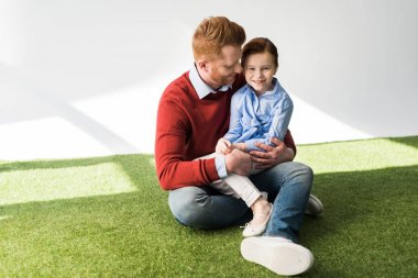 happy redhead father and daughter sitting together on grass