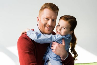 happy redhead father and daughter hugging and smiling at camera on grey