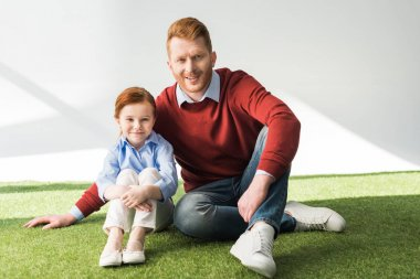 happy redhead father and daughter sitting on grass and smiling at camera on grey