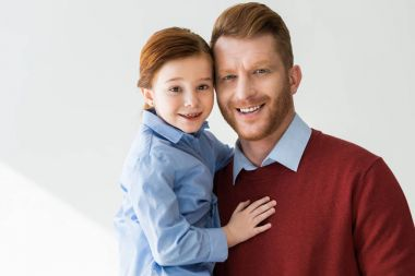 happy redhead father and daughter embracing and smiling at camera on grey