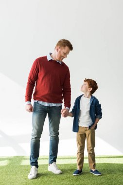 happy redhead father and son holding hands and smiling each other on grey