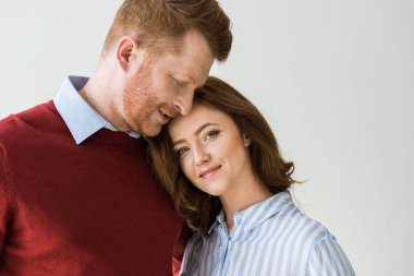 portrait of beautiful happy redhead couple standing together isolated on grey