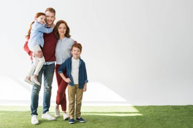 happy redhead family with two kids standing together and smiling at camera on grey