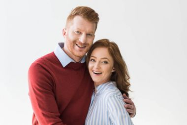 portrait of cheerful redhead couple standing together and smiling at camera isolated on grey