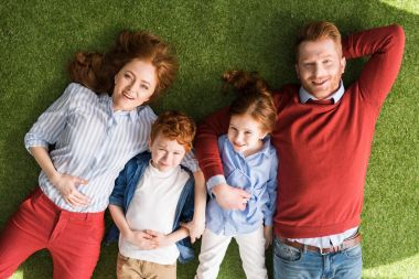 top view of happy redhead family with two kids lying together on grass and smiling at camera