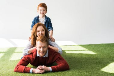 happy redhead family with one child lying together on grass and smiling at camera on grey