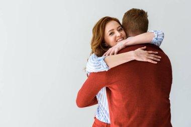 happy young couple hugging isolated on grey