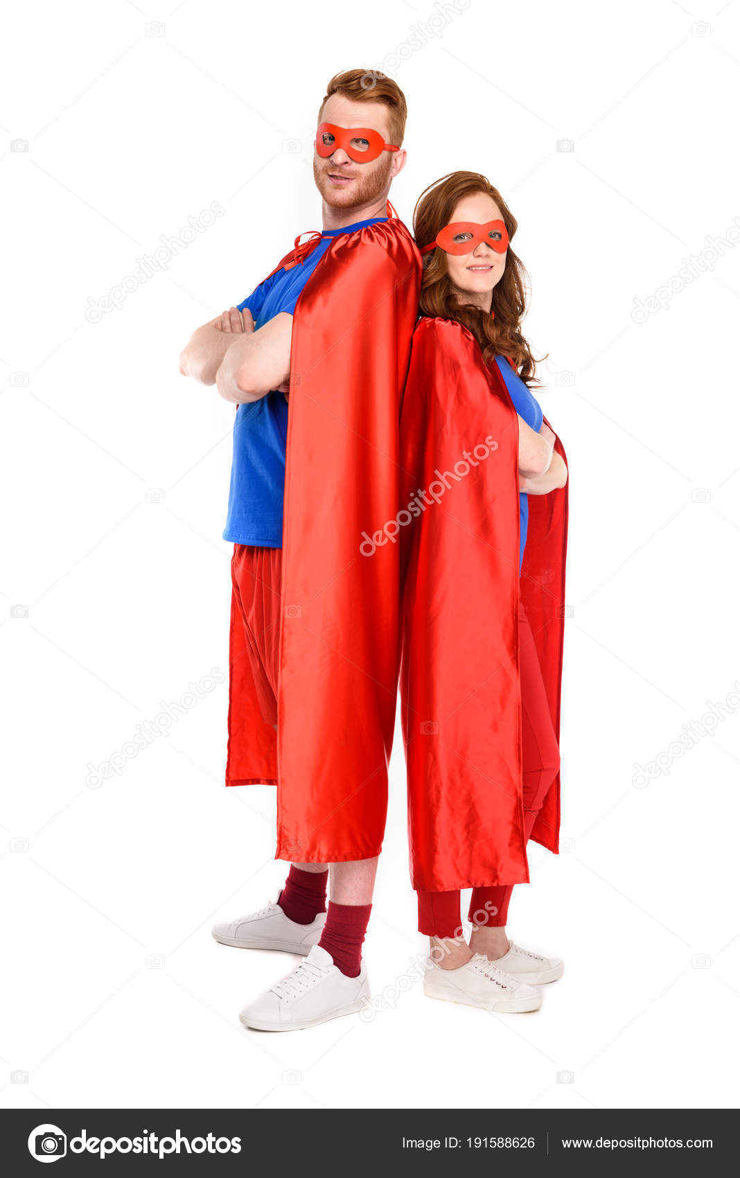 full length view couple superheroes costumes standing crossed arms